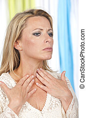 Mature woman with hands at her throat