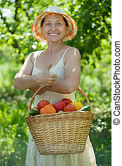 mature woman with harvested vegetables