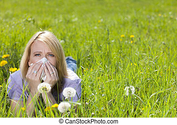 Mature woman with hayfever and handkerchief in the grass