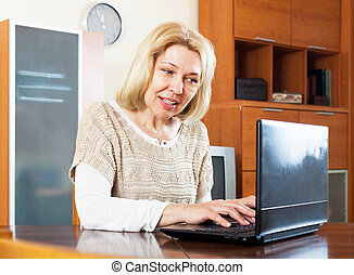 mature woman  with laptop  at table