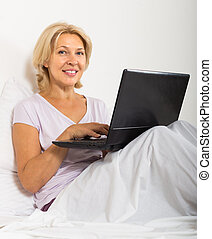 Mature woman with laptop in bed