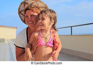 mature woman with little girl on veranda