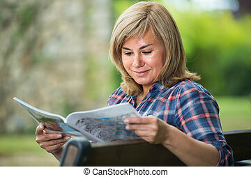 mature woman with magazine in garden .