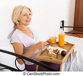 Mature woman with orange juice, berries and yogurt