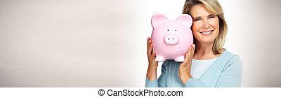 Mature woman with piggy bank.