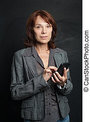 Mature woman with smartphone on blackboard background