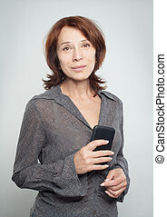 Mature woman with smartphone on white
