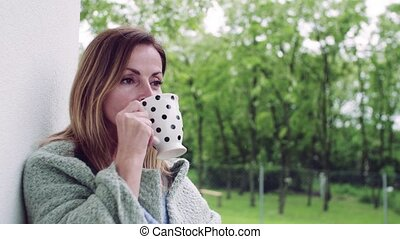 Mature woman with tea and blanket standing outdoors on ...