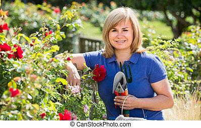 mature woman with tools in garden.
