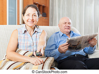 mature woman with TV remote against  man with newspaper