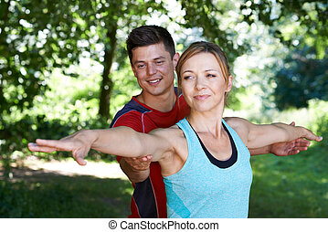 Mature Woman With Yoga Coach In Park