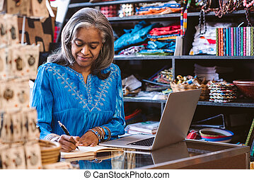 Mature woman working at a counter in her fabric shop