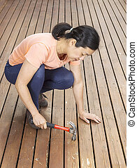 Mature woman working on Deck with Hammer