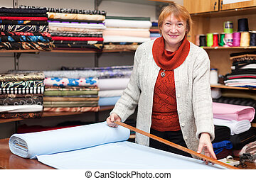 woman works at fabric store - Mature woman works at fabric...