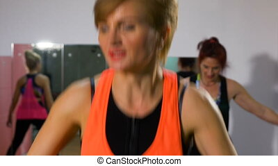 Mature women fitness instructor doing energetic aerobics session at the gym