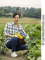 Mature women kneeling in vegetable Garden