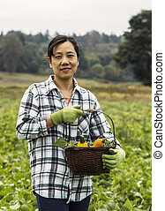 Mature women standing with vegetable basket in field