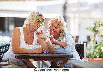 Mature women using smart watch in street cafe