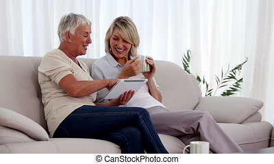 Mature women using tablet pc on the couch while having a hot...