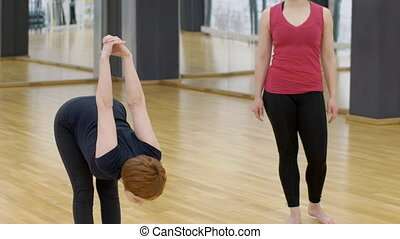 Mature yoga instructor is showing the exercise to young lady in modern gym, slow motion.