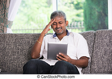 matured indian male in stress worry look with a tablet on a sofa