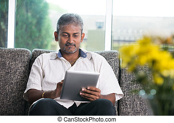 matured indian male with a tablet on a sofa setting