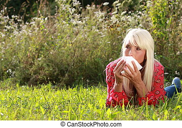Matured woman lying in gras with handkerchief
