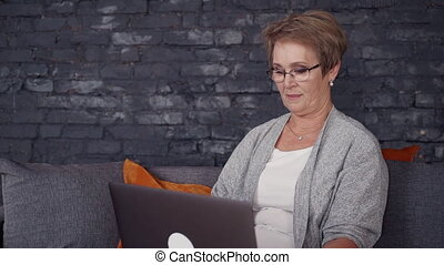 Matured woman spending free time with laptop at house -...