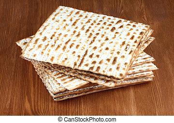 Matzah on wooden table - matzo flatbread for Jewish high...