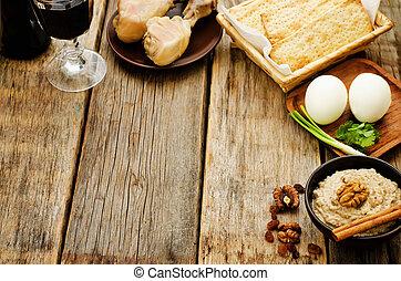 Matzah, wine, eggs, chicken, greens and haroset on a dark...
