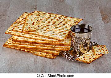 Matzah with kiddush cup of wine - Closeup of Matzah with...