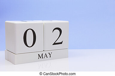May 02st. Day 2 of month, daily calendar on white table with reflection, with light blue background. Spring time, empty space for text