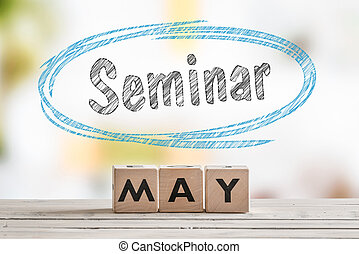 May seminar sign on a wooden table