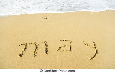 May - written in sand on beach texture
