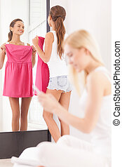 Maybe this dress? Beautiful young woman holding dress and looking at the mirror while another women sitting on the foreground and looking at the mobile phone