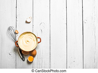 Mayonnaise in bowl with whisk.