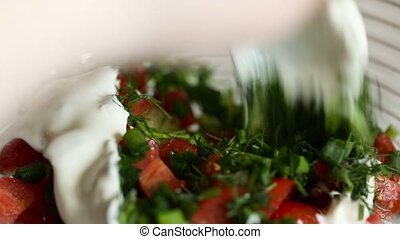 Mayonnaise is added to a bowl with the cut vegetables and...