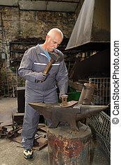 mayor masculino, herrero, utilizar, martillo, encima, yunque