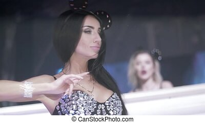 MC girl in mouse ears, crystals bodysuit dance, sing on stage of nightclub.