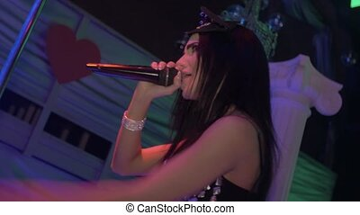 MC girl in mouse ears, crystals bodysuit, heels sing on stage of nightclub.