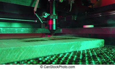 MDF laser cutting machine close up cuts wooden board with ...