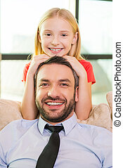 Me and my father. Cute little girl bonding to her cheerful father sitting on the couch at home
