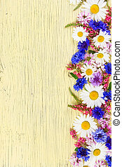 Meadow flowers on yellow rustic wooden background.