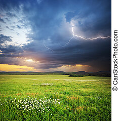 Meadow in mountain. Rain cloud and lightning. Nature...