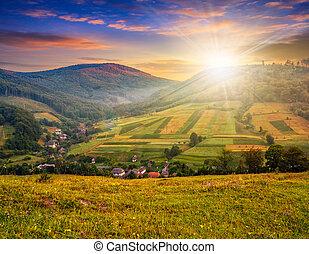meadow near village in autumn mountains at sunset - village...