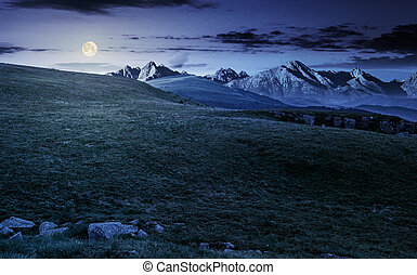 meadow with huge stones on top of mountain range at night -...