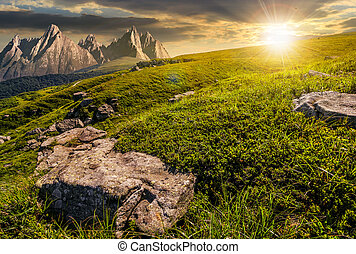 meadow with huge stones on top of mountain range at sunset -...
