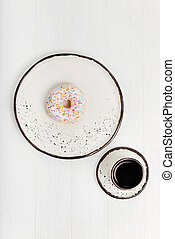 Quick snack for quick start. Simple light morning meal consisting of a sweet doughnut and a cup of coffee being served on white clay plates which are standing on a white table