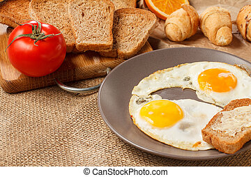 Meal for breakfast. Plate with fried eggs, toast with butter, croissants, bread