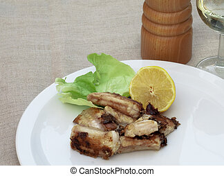 Meal of fried conger with lemon and a glass of white wine